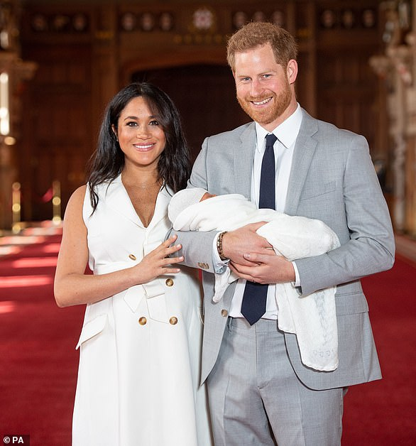 The Duke and Duchess of Sussex are pictured with their baby son in the majestic setting of St George's Hall at Windsor Castle today