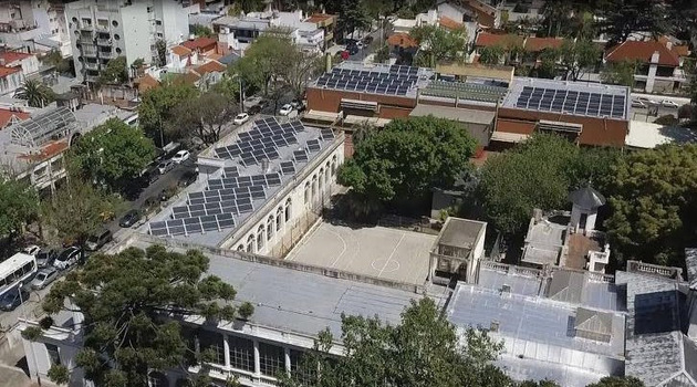 Aerial view of the rooftops of the primary and secondary schools located across from the main square in Villa Devoto, a residential neighborhood in the Argentine capital. The adjacent schools now have 200 solar panels with an installed capacity of 70 kilowatts, and the surplus is injected into the Buenos Aires electricity grid. Credit: Courtesy of Buenos Aires city government