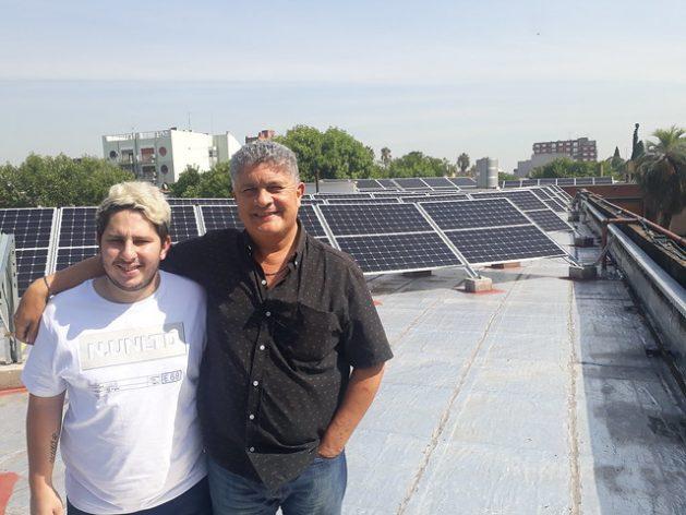 Sebastián Ieraci (L), a member of the group of students who in 2014 pushed for the switch to solar energy at the Antonio Devoto High School, stands next to the school's principal Marcelo Mazzeo on the rooftop of the educational institution located in the Buenos Aires neighbourhood of Villa Devoto. Credit: Daniel Gutman/IPS