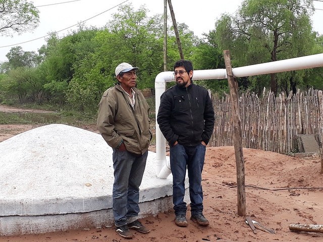 Mariano Barraza of the Wichí indigenous community (L) and Enzo Romero, a technician from the Fundapaz organisation, stand next to the tank built to store rainwater in an indigenous community in the province of Salta, in the Chaco ecoregion of northern Argentina, where there are six months of drought every year. CREDIT: Daniel Gutman/IPS