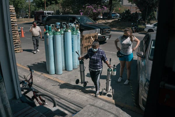 An employee carries oxygen tanks to refill them at an uncertified private oxygen provider in Mexico City this month. In Mexico, hospitals have been so overrun that virus patients have been dying in their homes, gasping for air because there are not enough oxygen tanks to meet the need. As many as 20 poor countries were in urgent need of oxygen.