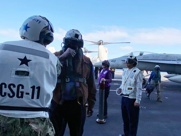 Defense Secretary Lloyd J. Austin III greeting troops aboard the carrier Nimitz on Thursday.