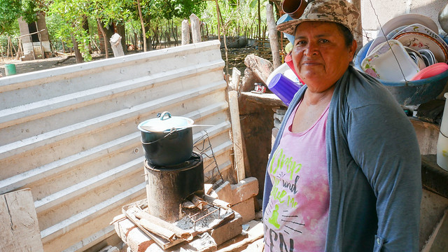 Petrona Cañénguez shows how she cooks bean soup on an energy-efficient rocket stove in an outside room of her home in the hamlet of San Sebastián El Chingo, one of the beneficiaries of a sustainable development programme in the municipality of San Luis La Herradura, on El Salvador's southern coast. CREDIT: Edgardo Ayala /IPS