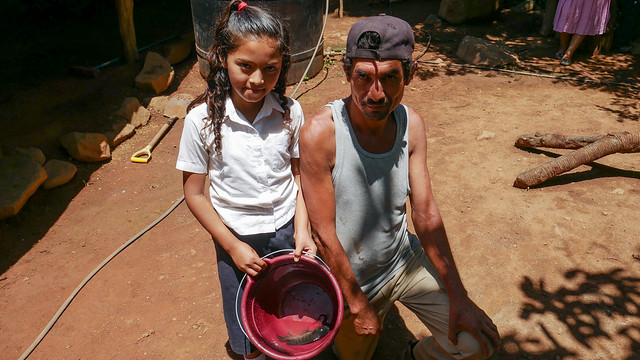 Cristino Martínez and one of his daughters show the tilapia they have just caught in the family pond they have dug in the backyard of their home in the village of El Guarumal in the eastern department of Morazán, El Salvador. The large peasant family raises fish for their own consumption and not for sale. CREDIT: Edgardo Ayala/IPS