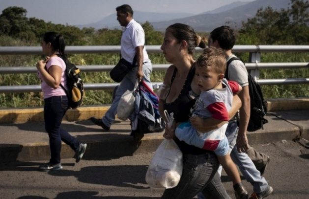 A Venezuelan family carrying a few belongings crosses the Simon Bolivar Bridge at the border into Colombia. Over the years, the migration flow has grown due to increasing numbers of people with unsatisfied basic needs. CREDIT: Siegfried Modola/UNHCR